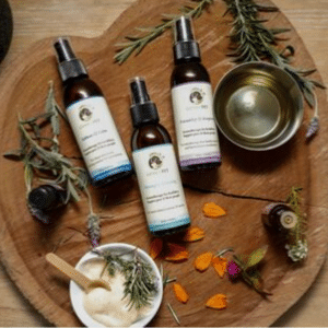 Genki Pet Aromatherapy for pets and their people three bottles of behaviour changing spritzes on natural wood with herbs and essential oils and flowers