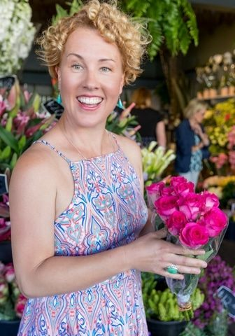 Natural Therapies for Pets Woman holding pink roses in front of florist shop