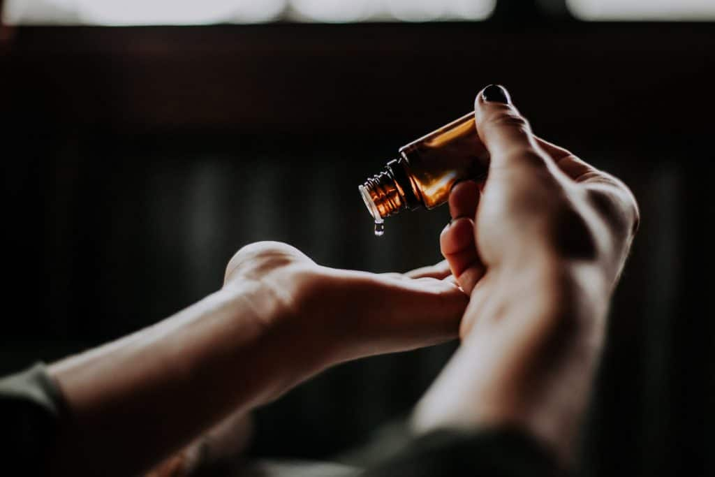 which Essential Oils are safe for my doggenki pet aromatherapy for pets and their people essential oil bottle dropping oil into woman's hand